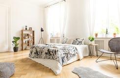 Sedia nera vicino al letto con gli strati modellati nel inte bianco della camera da letto Immagini Stock Libere da Diritti