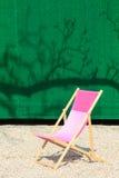 Sedia pieghevole davanti alla parete verde Fotografie Stock Libere da Diritti