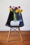 Sedia pranzante nera contemporanea con i fiori gialli e porpora Fotografia Stock