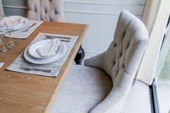 Sedia pranzante piacevole alta chiusa con gli insiemi di legno del piatto e della tavola Immagine Stock Libera da Diritti