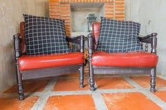 Sedia rossa d'annata e cuscino nero nella stanza fotografia stock libera da diritti
