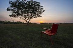 Sedia rossa in tramonto e cielo di pendenza Fotografie Stock Libere da Diritti