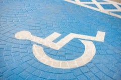 Sedia a rotelle blu di handicap che segna un posto-macchina riservato fotografie stock