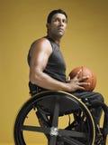 Sedia a rotelle di With Basketball In dell'atleta del paraplegico Fotografia Stock