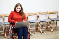 Sedia a rotelle di seduta ed impianti della bella donna disabile caucasica con il computer portatile dell'interno Fotografia Stock Libera da Diritti