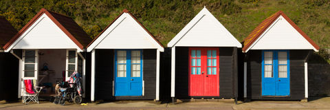 Sedia a rotelle e capanne colourful della spiaggia con le porte blu e rosse in un panorama inglese tradizionale della struttura d Immagini Stock