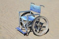 sedia a rotelle isolata fatta di alluminio sulla sabbia della spiaggia Fotografia Stock