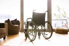 Sedia a rotelle vuota in salone accanto allo strato Fotografia Stock Libera da Diritti