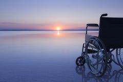 Sedia a rotelle vuota sul lago al tramonto con i bei colori fotografia stock
