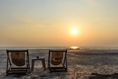 Sedia a sdraio del Wo sulla spiaggia con la luce di tramonto Fotografia Stock Libera da Diritti