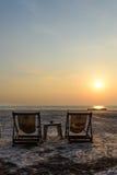 Sedia a sdraio del Wo sulla spiaggia con la luce di tramonto Immagini Stock