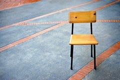 Sedia sul pavimento di calcestruzzo all'aperto con il pavimento dei mattoni Fotografia Stock