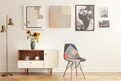 Sedia variopinta che sta in interno bianco del salone con la galleria sulla parete, armadietto con i fiori e tazze di tè immagini stock