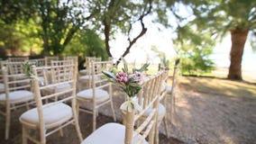 Sedie ad una cerimonia di nozze Decorato con le disposizioni dei fiori stock footage