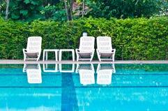 Sedie bianche accanto alla piscina Fotografie Stock Libere da Diritti