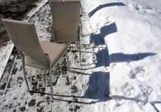 Sedie bianche che stanno nella neve Immagine Stock