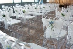 Sedie bianche con i fiori per una cerimonia di nozze Fotografia Stock