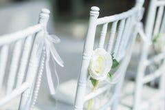 Sedie bianche con i fiori per una cerimonia di nozze Immagini Stock Libere da Diritti