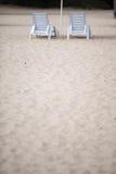 Sedie bianche dello stagno sulla spiaggia di sabbia Immagine Stock