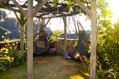Sedie d'attaccatura del vimine nel giardino con il fondo verde della natura Fotografia Stock Libera da Diritti