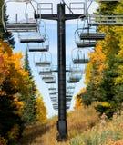 Sedie dell'ascensore di sci e fogliame di caduta vuoti Fotografia Stock