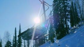 Sedie dell'ascensore di sci il giorno di inverno Ascensore di sci moderno della sedia nella stazione sciistica la gente guida la  Fotografie Stock