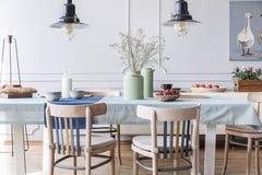 Sedie di legno alla tavola con i fiori e l'alimento nell'interno bianco della sala da pranzo del cottage con le lampade ed il man fotografie stock libere da diritti
