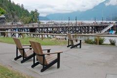 Sedie di legno sulla spiaggia vicino al pilastro, baia a ferro di cavallo fotografia stock libera da diritti