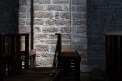 Sedie di legno in una chiesa scura, illuminazione sottile sulla parete di pietra Immagini Stock