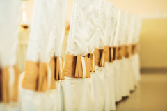 Sedie di nozze nella fila decorate con il nastro dorato di colore Fotografia Stock