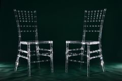 Sedie di plastica trasparenti su un fondo verde in un perno della foto Fotografia Stock Libera da Diritti