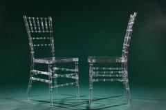 Sedie di plastica trasparenti su un fondo verde in un perno della foto Immagine Stock