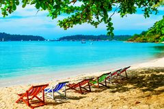 Sedie di salotto vuote nella tonalità sulla spiaggia Isola di paradiso per le feste ed il rilassamento immagini stock