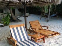 Sedie di spiaggia alla riva dell'Oceano Indiano fotografie stock