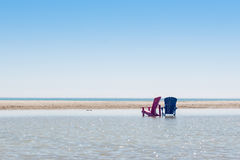 Sedie di spiaggia che stanno nell'acqua un giorno soleggiato fotografie stock libere da diritti