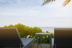 Sedie di spiaggia con la tavola sulla spiaggia sotto la palma davanti al mare Sguardo in avanti al mare Può essere l'uso come fon Immagine Stock