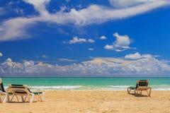 Sedie di spiaggia dall'acqua del turchese su una spiaggia tropicale nella C fotografie stock