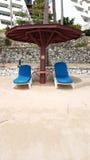 Sedie di spiaggia di legno bianche con il cuscino blu e tonalità di legno sulla t Fotografie Stock Libere da Diritti