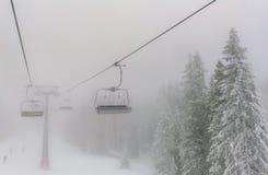 Sedie di un'intestazione dell'ascensore di sci nella nebbia Fotografia Stock Libera da Diritti