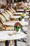 Sedie di vimini e tavole di pietra con i fiori conservati in vaso nel giardino Immagini Stock Libere da Diritti