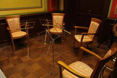Sedie e partitura dei supporti di musica per l'orchestra di archi (quartetto) Immagini Stock