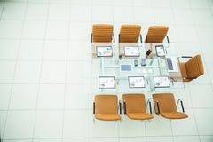 Sedie e scrittorio con i documenti e computer portatile per i negoziati con i soci commerciali Immagini Stock