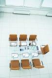 Sedie e scrittorio con i documenti e computer portatile per i negoziati con i soci commerciali Immagine Stock