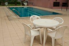 Sedie e tavola accanto alla piscina dentro il aparment e uff Fotografia Stock