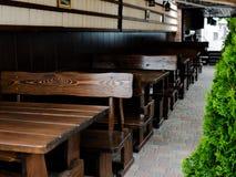 Sedie e tavole di legno all'aperto con la disposizione laterale della disposizione dei posti a sedere quattro sul prato inglese d fotografie stock