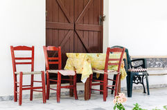 Sedie e tavole di legno alla locanda greca tradizionale Immagini Stock