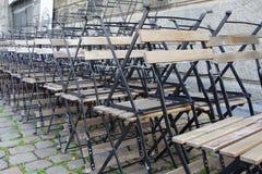 Sedie e tavole di legno impilate sulla via vuota nel primo mattino fotografia stock
