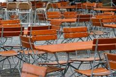 Sedie e tavole inoccupate in un ristorante del giardino con le gambe della tavola e le gambe della sedia fatte di ferro e delle c Fotografie Stock