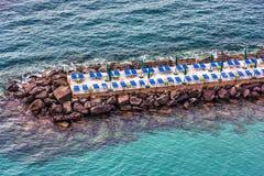 Sedie ed ombrello di spiaggia su un frangiflutti a Sorrento immagine stock