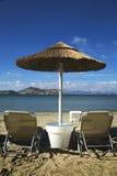 Sedie ed ombrello prendenti il sole sulla spiaggia Fotografia Stock